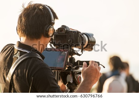 Video camera man operator working with professional equipment,filming recording #630796766