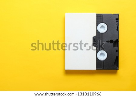 Video cassette in cover, videotape on a yellow background. Top view, minimalism