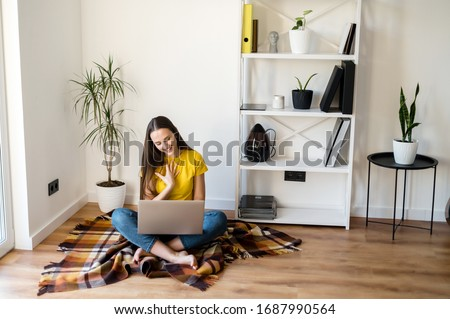 Video communication, zoom. Young positive woman in a yellow casual t-shirt communicates via video communication using a laptop at home