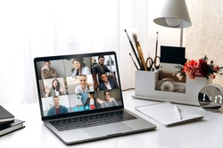 Video conference by laptop. On the laptop screen, colleagues who gathered in a video conference to work on-line. The laptop is on the work desk at home