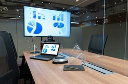 Video conference meeting room with clear acrylic sheet separates the center on the conference table to prevent COVID-19 and face shield on the table.