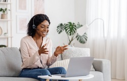 Video Conference. Smiling african woman having web call on laptop at home, talking at camera while sitting on sofa in living room