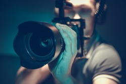 Video Content Creating. Caucasian Filmmaker with DSLR Camera Taking Shoots For His New Production. Videography Theme.