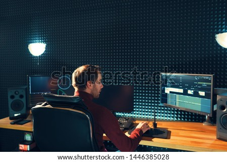 Video editing. Professional editor adding special sound effects. Back view of young man watching graphs on monitors. Copy space on gray wall Stock foto ©
