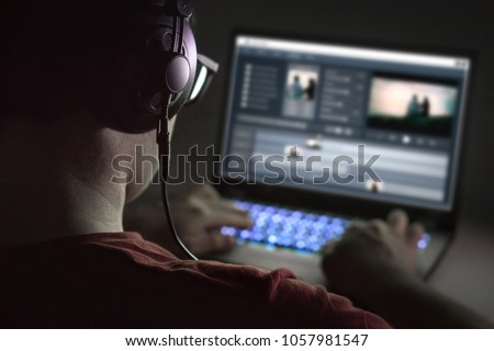 Video editing with laptop. Professional editor adding special effects or color grading footage. Back view of young man using computer software and wearing headphones.