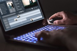 Video editing with laptop. Professional editor adding special effects or color grading footage for commercial film or movie. Man using software in computer.