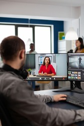 Video editor talking with remote customer in web online meeting using video call editing project, getting feedback on commercial movie using post production program on two displays in creative agency