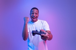 Video Gaming Concept. Euphoric African American Guy With Joystick Celebrating Game Win, Cheerful Black Man Raising Fist And Exclaiming With Excitement, Standing In Neon Light Over Purple Background
