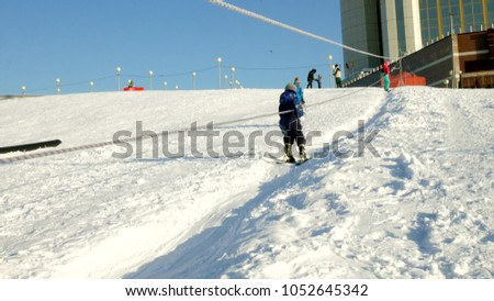 Video of snow ski slopes, lift lines and valley of Park in the Wasatch . Sunny day with families on skis and snowboards. Colorful winter warm clothes. Looking down slope to resort. 4k #1052645342