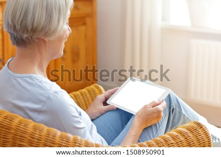 Video phone mock-up template: elderly woman at home talking with tablet computer on her lap, white screen.