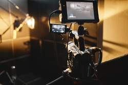 Video production backstage. Behind the scenes of creating video content, a professional team of cameramen with a director filming commercial ads. Video content creation, video creation industry. Low
