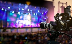 Video production covering event on stage by professional video camera in outdoor concert at sunset