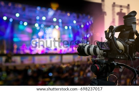 Video production covering event on stage by professional video camera in outdoor concert at sunset #698237017