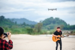 Video recording with a drone plane Asian men using video drones to make music videos