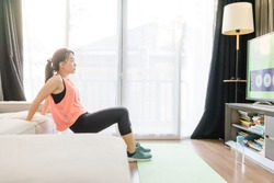Video streaming Stay home.home fitness workout class live streaming online.Asian woman doing strength training cardio aerobic dance exercises watching videos in the living room at home.Covid-19.