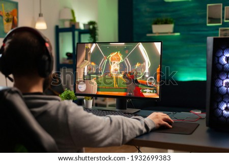 Videogamer looking into powerful computer playing virtual shooter game late at night in living room. Online streaming cyber performing during gaming tournament using technology network wireless