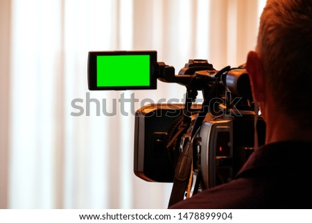 Videographer at work removes the story for the news. Green LCD display on high definition television camera. Template template for the design of information about the TV. #1478899904