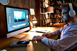 Videographer editor film maker wears headphones using digital software on desktop computer editing video footage visual content working at home office using post production multimedia making montage.
