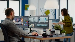 Videographer edits video project and cuts footage and sound using post production software and two monitors taking notes. Man processing film montage in digital multimedia star up company