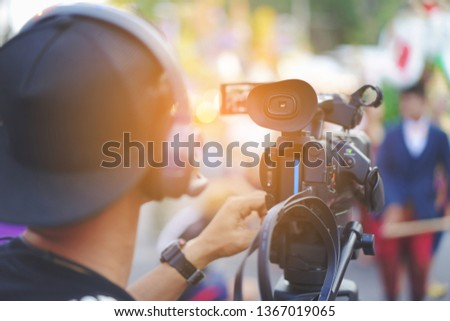 Videographer or operator shoots on Video camera with a transmitting device over Wi-Fi,Video production, headphones. live stream.  Cameraman using professional digital video camera. Outdoor setup  #1367019065