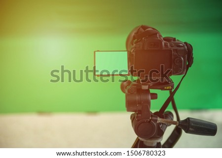Videographer taking video camera, camera equipment film stand by on green screen. #1506780323