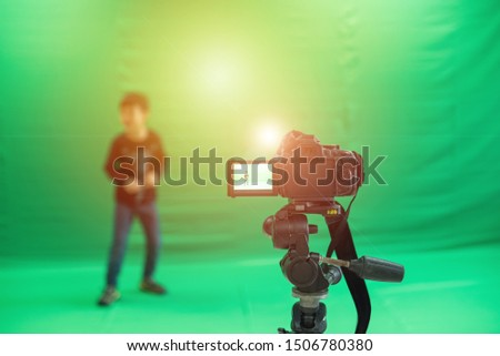 Videographer taking video camera, camera equipment film stand by on green screen. #1506780380