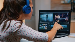 Videographer working on laptop from home, editing video and audio footage at night. Woman content creator using professional device modern technology network wireless processing film montage.