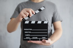 videography and filmmaking concept - clapper board in male hands over grey