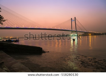 Vidyasagar bridge (setu) on river Hooghly at twilight with city lights reflections. The Hooghly bridge is the longest cable stayed bridge in India. #518280130