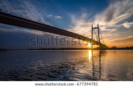 Vidyasagar Setu bridge at sunset with moody sky. This is the longest cable stayed bridge in India. #677394781