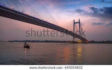 Vidyasagar Setu bridge on river Hooghly with wooden boat after sunset. This bridge is the  longest cable stayed bridge in India. #645054832