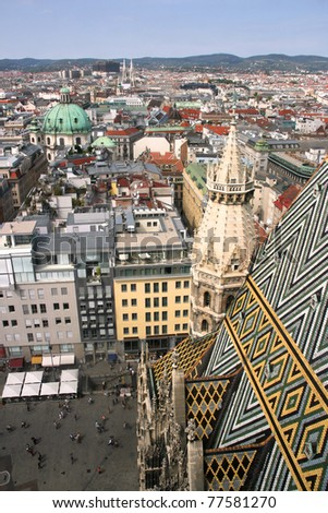 Vienna aerial view - old town down there and financial district skyscrapers in the background. Stephansdom cathedral roof in the foreground.