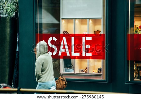 VIENNA, AUSTRIA - JULY 05, 2011: Woman passing in front of large window of luxury store with red on white letters SALE. Vienna is a magnetic attraction for tourists from across the world