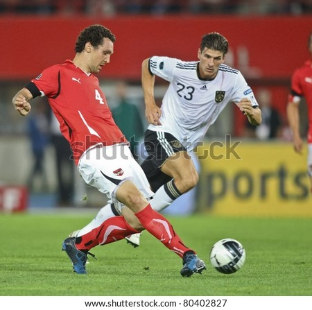VIENNA,  AUSTRIA - JUNE 3 Emanuel Pogatetz (No. 4, Austria) and Mario Gomez (No. 23, Germany) fight for the ball during the EURO 2012 soccer game on June 3, 2011 in Vienna, Austria. Austria loses 1:2