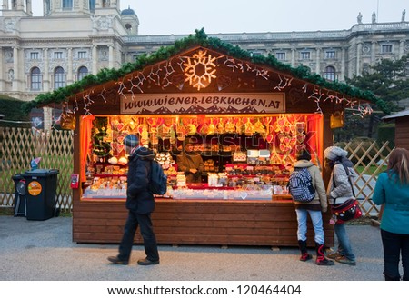 VIENNA, AUSTRIA - NOVEMBER 22: People walking at  Christmas Market at Maria-Theresien-Platz   in November 22, 2011 in Vienna, Austria.  Kiosk with cookies at Christmas market in Vienna