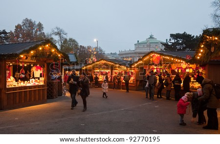 VIENNA, AUSTRIA - NOVEMBER 22: People walking at  Christmas Market at Maria-Theresien-Platz   in November 22, 2011 in Vienna, Austria. It sells Christmas gifts, candy and punch