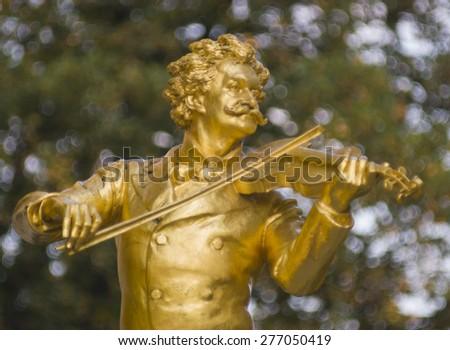 VIENNA, AUSTRIA - SEPTEMBER 14, 2003: Golden statue of music composer Johann Strauss, playing the violin, in the Stadtpark park.