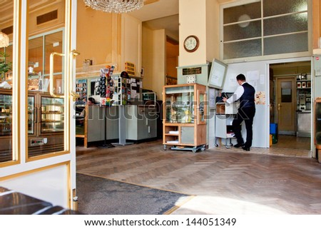 VIENNA - JUNE 5: Waiter in uniform stands at the cash register in the old cafe Westend in typical Viennese style with historical chairs and interior on June 5, 2013 in Vienna, Austria