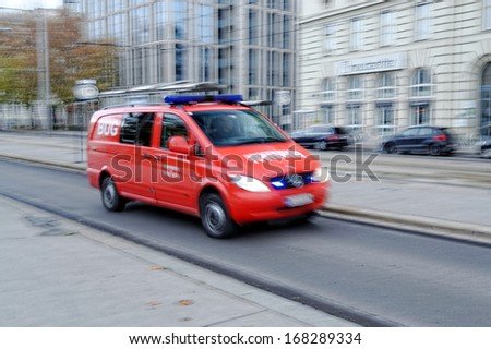 VIENNA - NOV 23. A fire rescue vehicle blazes by, it\'s sirens whaling in Vienna, Austria on November 23, 2013. An intentional motion blur gives a feeling of a rushed tension to the scene.