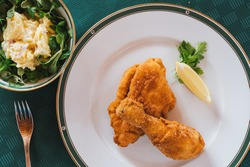 Viennese Fried Breaded Chicken wth Potatoe Mayonnaise Salad - A Tasty Classic Specialty o Austrian Cusine in the Style o Vienna