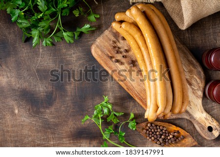 Viennese sausages on a wooden serving Board on a brown wooden table. Top view with a copyspace Stock photo ©