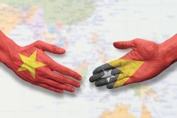 Vietnam and Timor-Leste - Flag handshake symbolizing partnership and cooperation