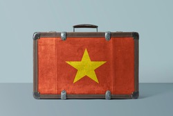 Vietnam flag on old vintage leather suitcase with national concept. Retro brown luggage with copy space text.