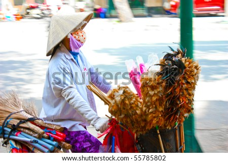 VIETNAM - JUNE 10: A Vietnamese broom and duster stall owner transports her products. June 10, 2010 Ho Chi Minh City, Vietnam - stock photo