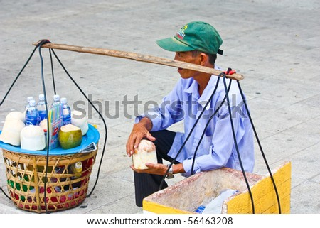 VIETNAM - JUNE 10: A Vietnamese drink seller holds a coconut in his hand and attempts to sell his drinks. June 10, 2010 Ho Chi Minh City, Vietnam