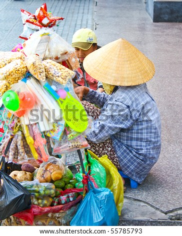 VIETNAM - JUNE 10: A Vietnamese lady sells various items along the sidewalk. June 10, 2010 Ho Chi Minh City, Vietnam