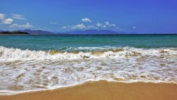 Vietnam. Summer. The white openwork foam of the waves falls beautifully on the clean sand. Aquamarine sea, blue sky. Silhouettes of mountains on the horizon. Clouds in the sky.