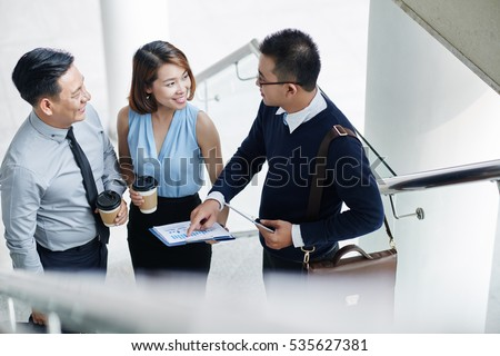 Vietnamese business people discussing financial report during the break