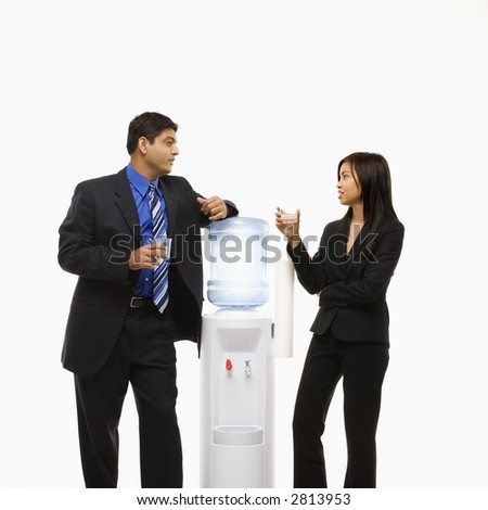 Vietnamese businesswoman and Indian businessman conversing at water cooler.