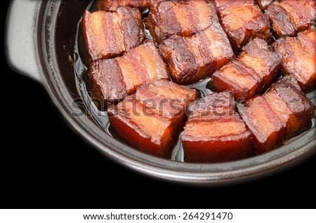 Vietnamese caramelized pork belly in clay pot on black background